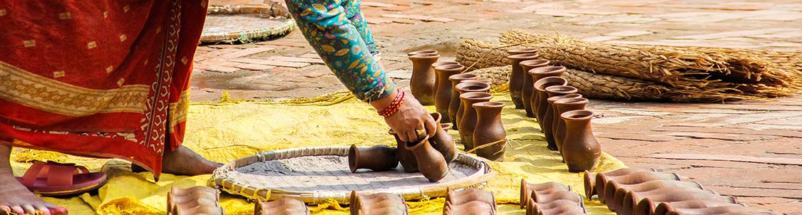 immagine di una donna che mette ad asciugare piccoli vasi di terracotta